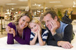 Family of three on bed in furniture shop, smiling, portrait