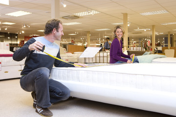 Man measuring bed in furniture shop, family in background