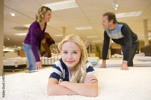 Girl (6-8) on bed in furniture shop, parents in background, smiling, portrait