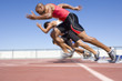 Sprinters leaving starting blocks, low angle view (blurred motion)