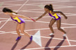 Female relay athletes passing baton (blurred motion)