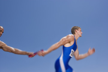 Relay athletes passing baton (blurred motion)