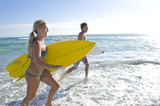 Young couple with surfboards in sea, side view