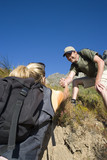 Young couple hiking, man helping woman up bank, low angle view