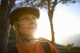 Young woman in bicycle helmet, smiling, close-up (lens flare)