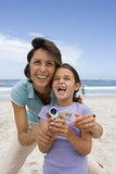 Mother embracing daughter (6-8) with camcorder on beach, smiling