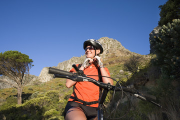 Young woman cycling in wilderness, low angle view