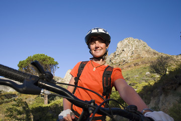 Young woman cycling in wilderness, smiling, portrait, low angle view