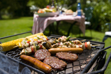 Food on barbecue by table in garden
