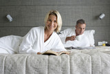 Couple in bathrobes on bed, man with mug reading, portrait of woman smiling