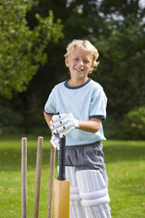 Boy (6-8) playing cricket, smiling, portrait