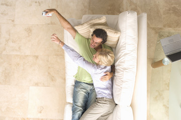 Young couple embracing on sofa, woman reaching for remote control from man, elevated view