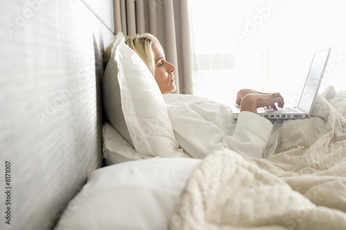 Woman with laptop computer in bed, side view