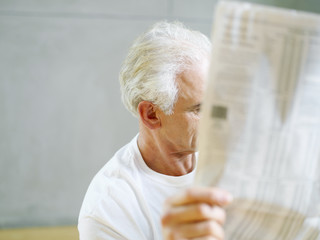 Mature man reading newspaper, newspaper obscuring face, elevated view
