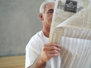 Mature man reading newspaper, close-up