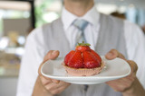 Waiter with strawberry tart, close-up of tart