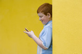 Boy (9-11) with mobile phone, smiling, side view