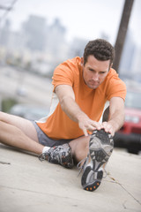 Male runner stretching on pavement (tilt)