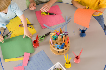 Pre-school children (3-5) at nursery with scissors and coloured paper at table, elevated view