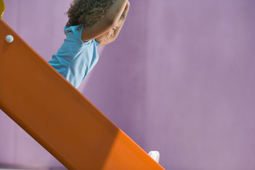 Girl (4-6) on slide, side view