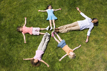 Woman with girls (4-8) lying on grass making star shape