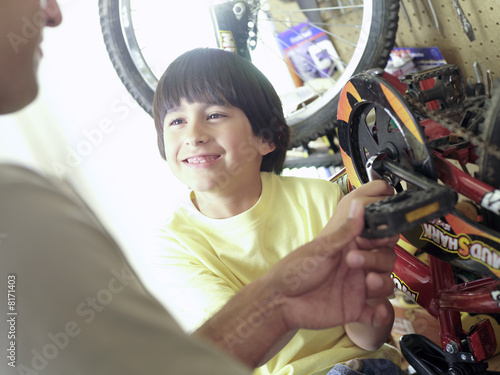 Father and son (7-9) fixing bicycle in garage, close-up of boy smiling