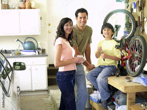 Family of three fixing bicycle in garage, smiling, portrait