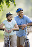 Mature couple cycling outdoors, smiling