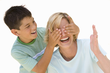 Boy (7-9) covering mother's eyes, smiling