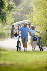 Mature couple walking with bicycles outdoors