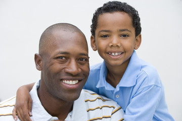 Portrait of father and son (6-8) smiling, close-up