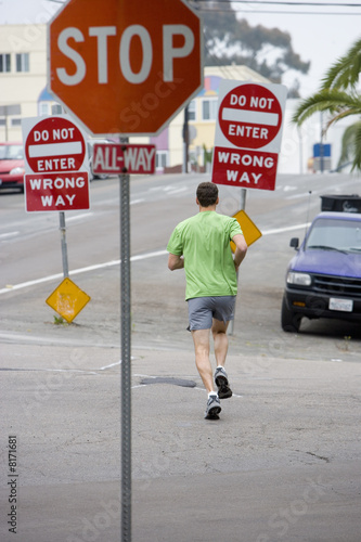 Man running by 'Stop' sign