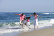 Family of four walking in waves on beach