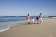Family of four walking on beach