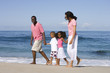 Family of four walking on beach