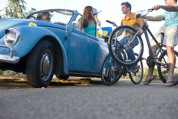 Men on bicycles in conversation with women in car, low angle view