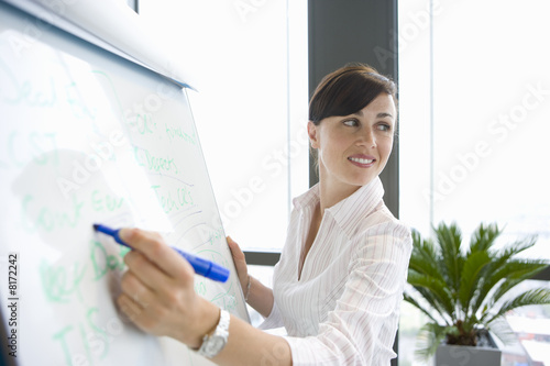 Woman writing on whiteboard