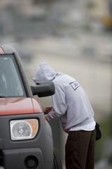 Man in hood unlocking car door
