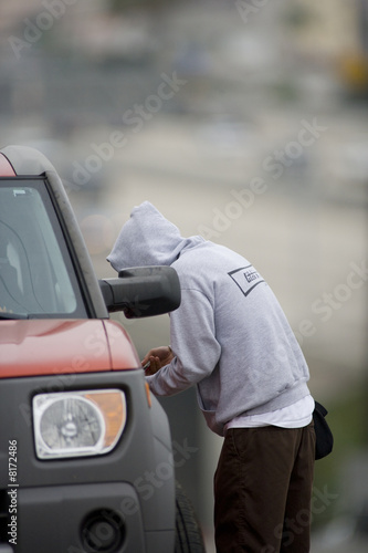 Man in hood unlocking car door