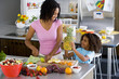 Woman making fruit salad with daughter (6-8)