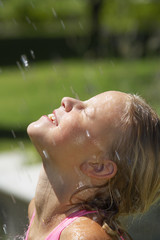 Girl (9-11) being sprinkled with water outdoors, smiling