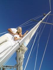 Senior couple erecting sail on yacht, low angle view (tilt)