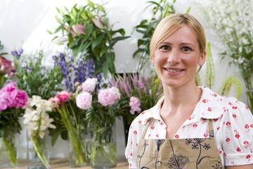 Female florist in shop, smiling, portrait