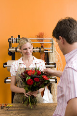 Female florist with bouquet for customer, smiling