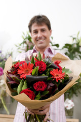Man with bouquet of flowers, smiling, portrait