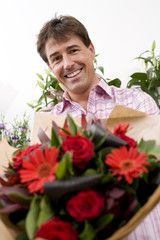 Man with bouquet of flowers, smiling, portrait, low angle view