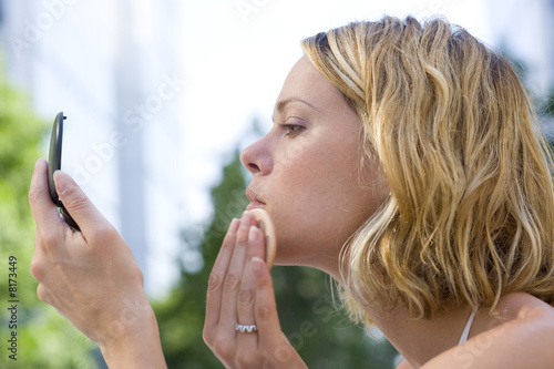 Young woman applying make-up, side view