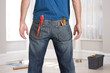 Man decorating, tools in pockets, rear view