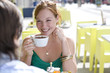 Young couple in cafe, outdoors, woman smiling at man