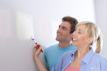 Couple painting colour samples on wall